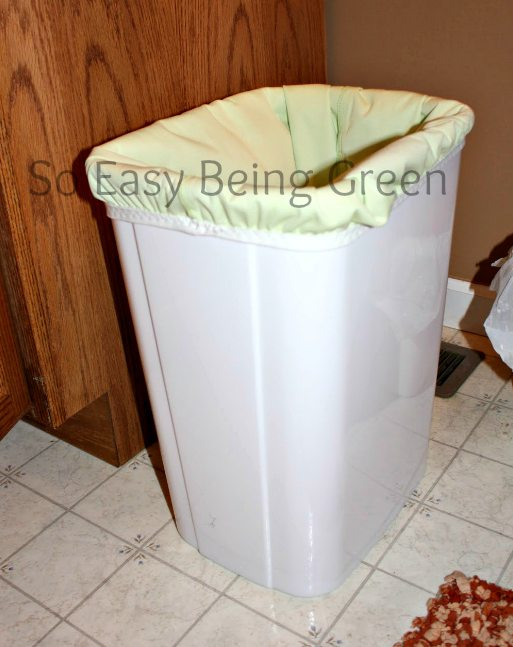 light green cloth diaper pail liner in white trash can