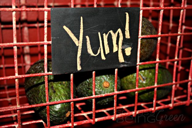 avocados in a basket with yum written on outside of basket