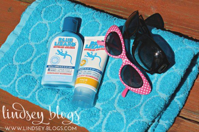 Blue Lizard Sunscreen with sunglasses on beach towel