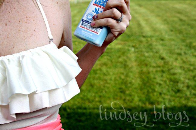 Fair Skin lady in bathing suit holding Blue Lizard Sunscreen