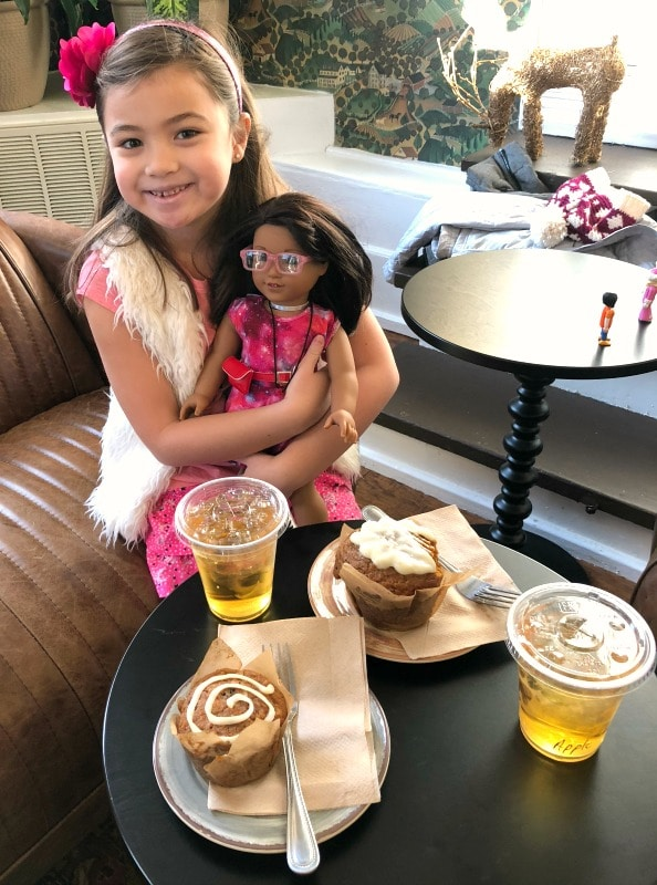 Girl holding American Girl doll in coffee shop