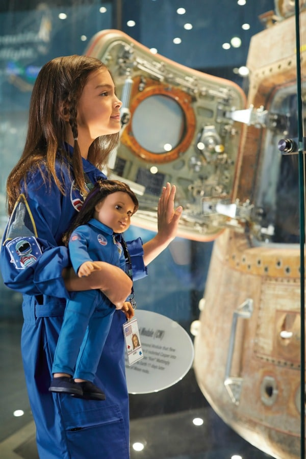 Girl in NASA jumpsuit with American Girl Luciana Vega