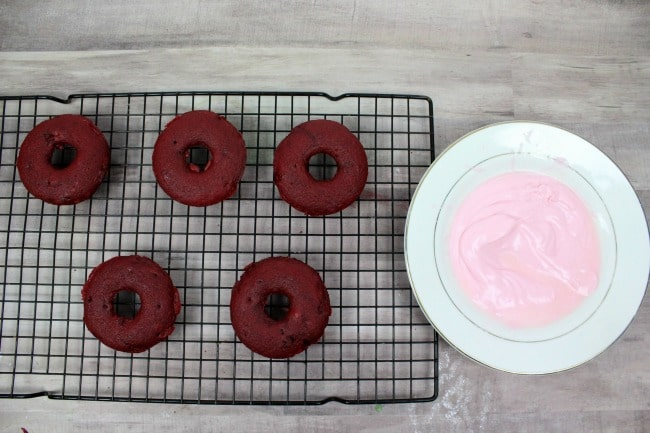 Red Velvet Donuts on cool rack with pink icing
