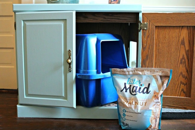 Bag of LitterMaid Walnut Shells cat litter in front of cat litter box cabinet