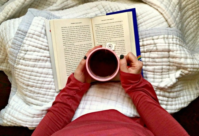 drinking tea while reading book with blanket