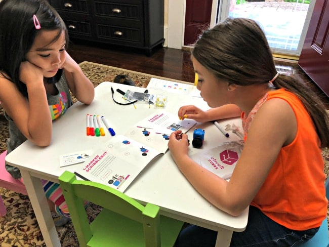 two girls reading instructions to create circuit cubes