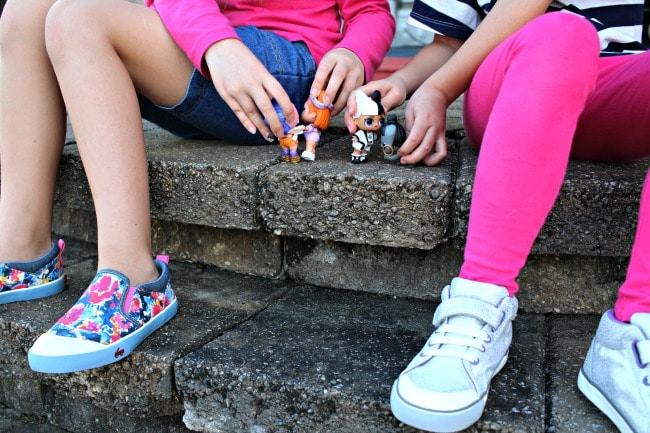 girls playing with lol dolls on steps