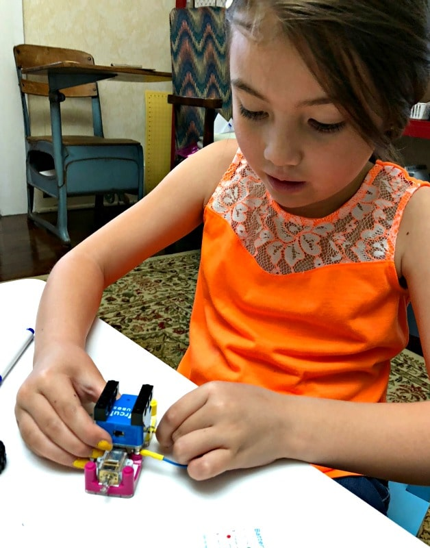 girl connecting circuit cubes with wires