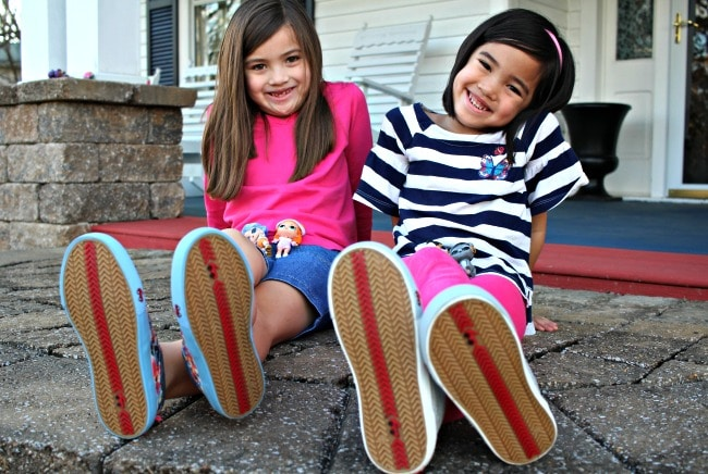 two girls sitting with shoes up