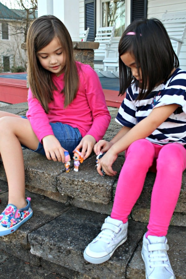 girls playing with lol dolls outside sitting on steps