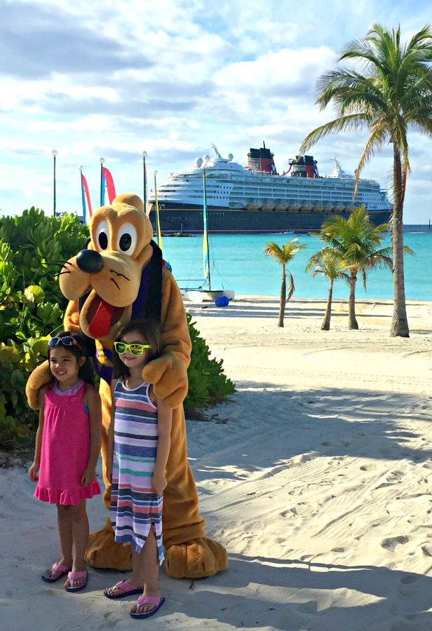 girls and pluto on castaway cay with disney magic in back