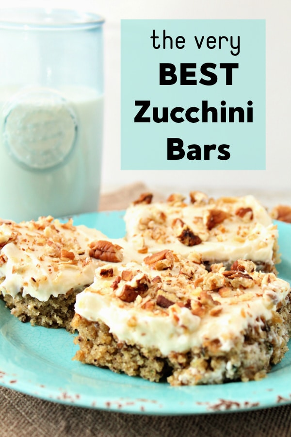 zucchini bars with frosting on blue plate with milk