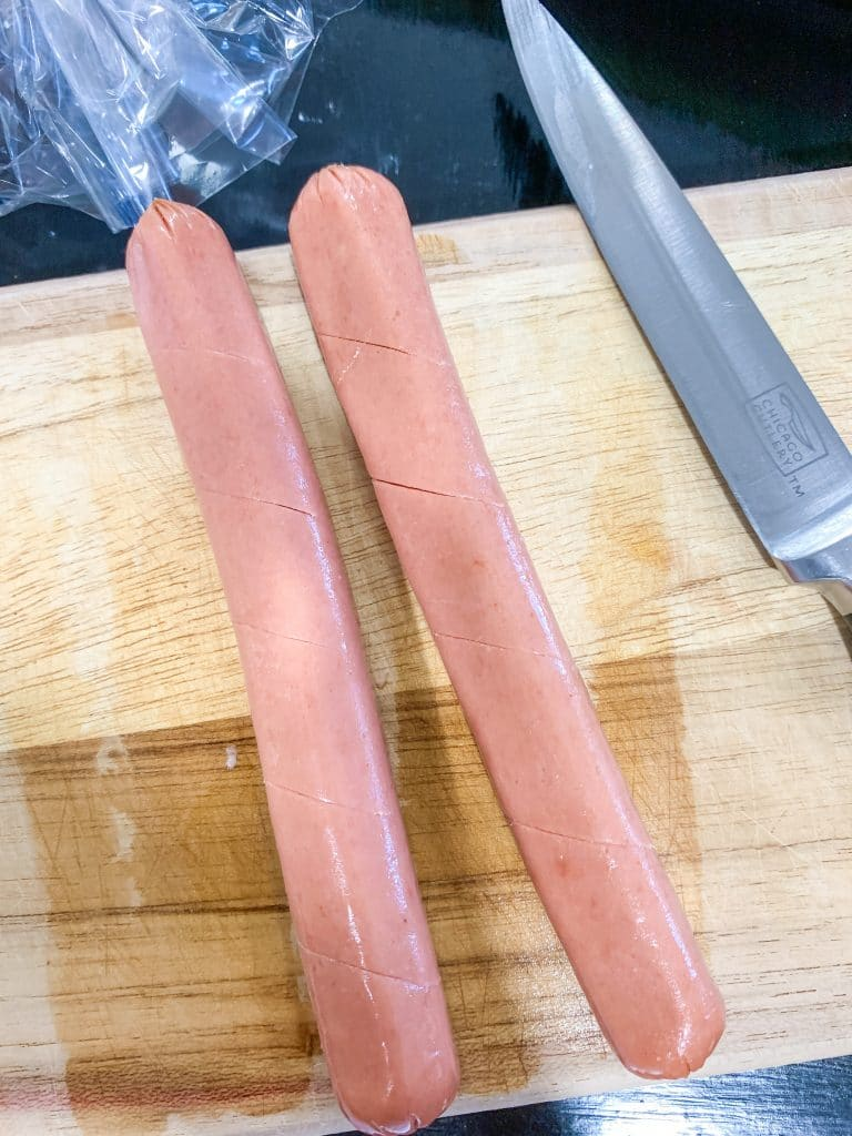 uncooked hot dogs with cuts on cutting board with knife