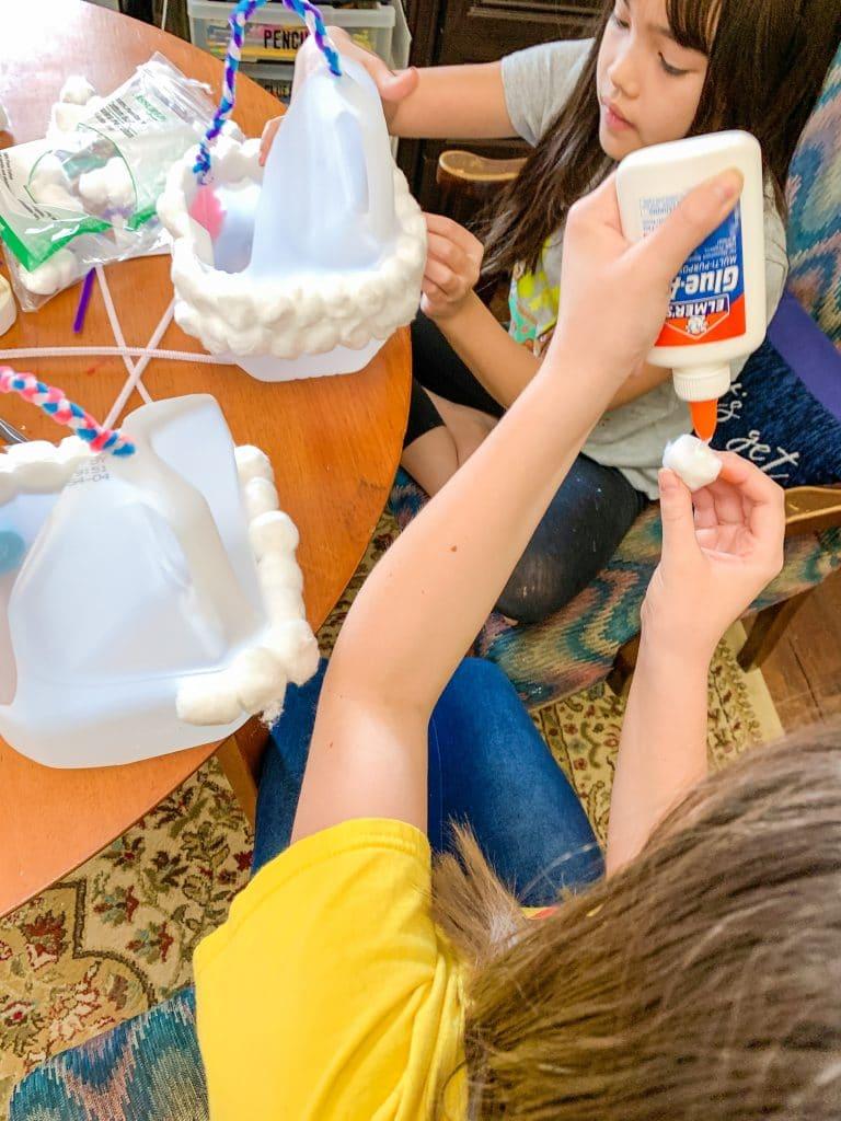 gluing cotton balls onto plastic milk jug