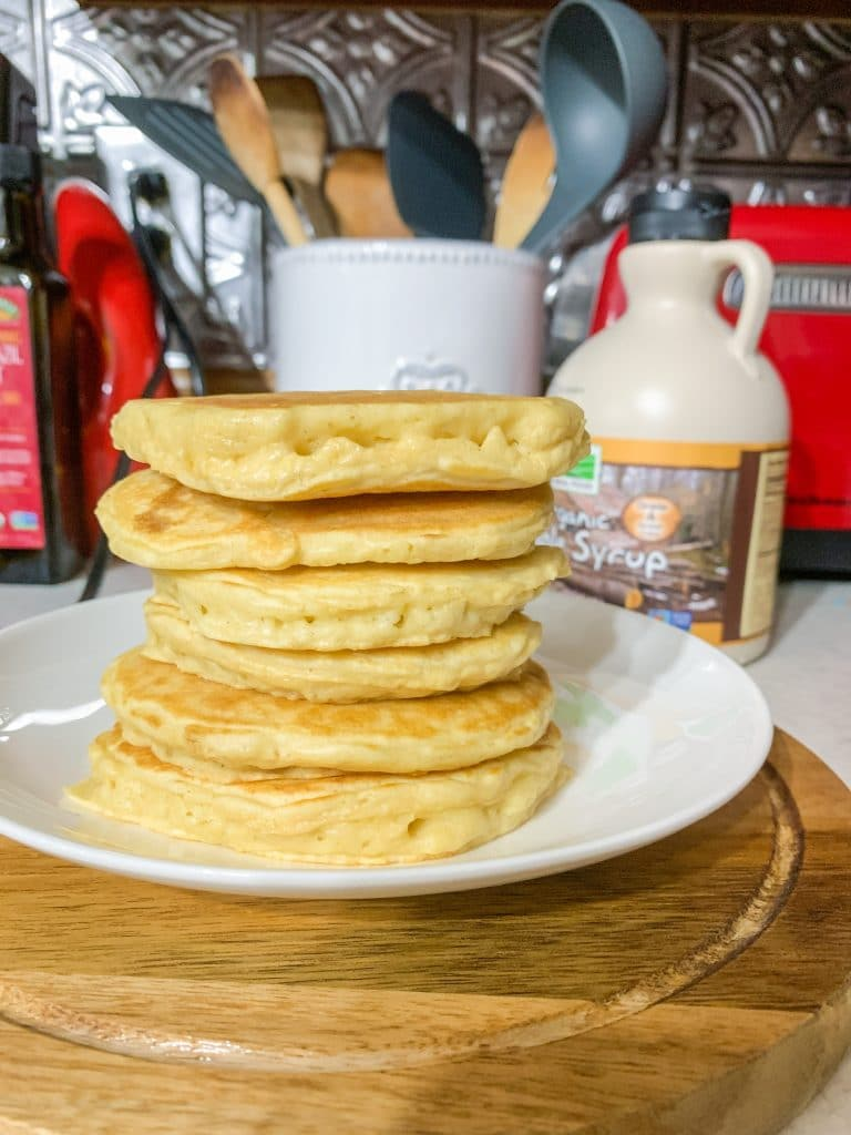 stack of almond milk pancakes on plate with maple syrup