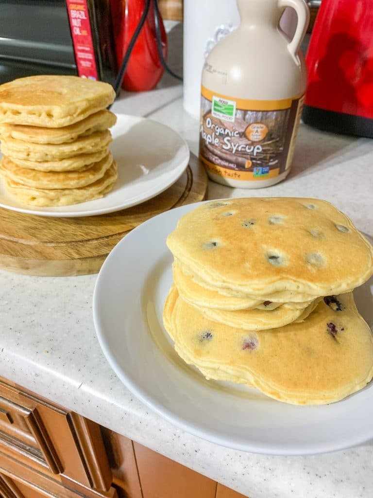 plates of almond milk pancakes with pancake add ins like blueberries