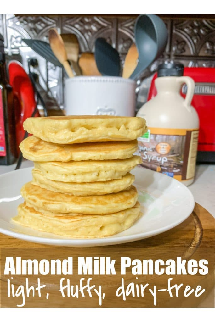 stack of almond milk pancakes on white plate and wooden cutting board